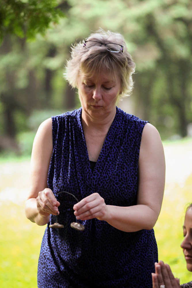 Reiki Master Susan Rouse ringing tingshaws to signify students have received their Reiki attunements